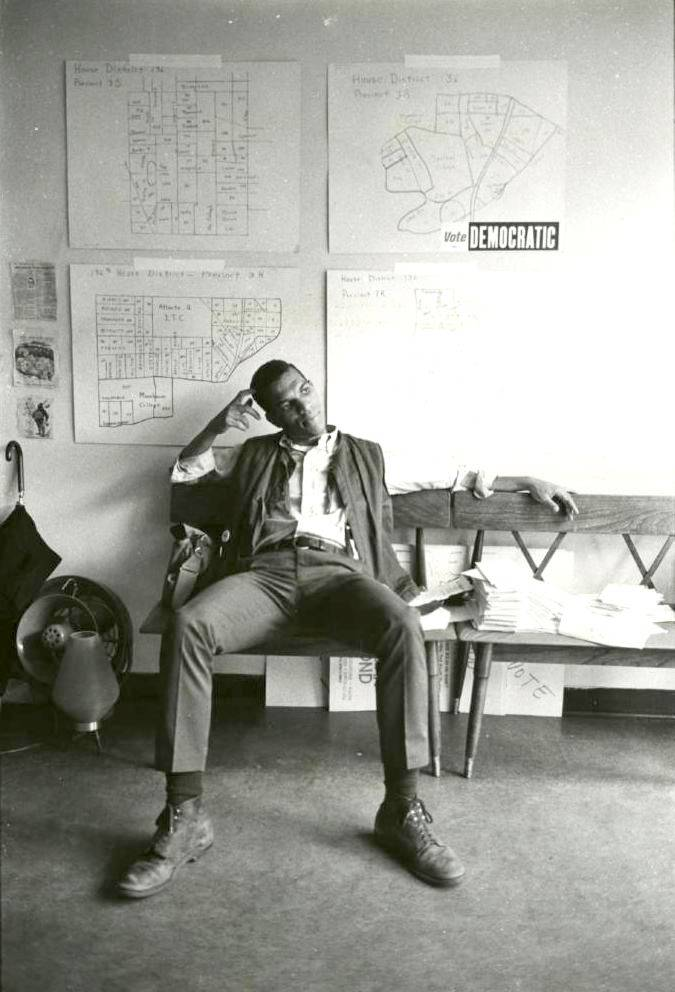 Ivanhoe Donaldson sitting in a campaign office, on the wall above him are maps of the voting districts around Atlanta